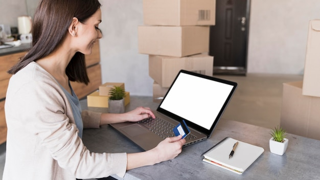 Vista lateral de la mujer que trabaja en el escritorio mientras sostiene la tarjeta de crédito