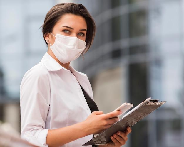 Vista lateral de la mujer que trabaja durante la pandemia con smartphone y bloc de notas