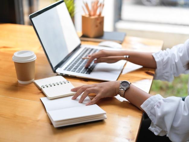 Vista lateral de la mujer que trabaja con el portátil y el material de oficina en la mesa de madera en el café
