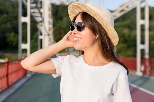 Vista lateral de la mujer que viaja sonriente en el puente con sombrero y gafas de sol