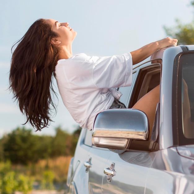 Vista lateral de la mujer recostada en la ventanilla del coche