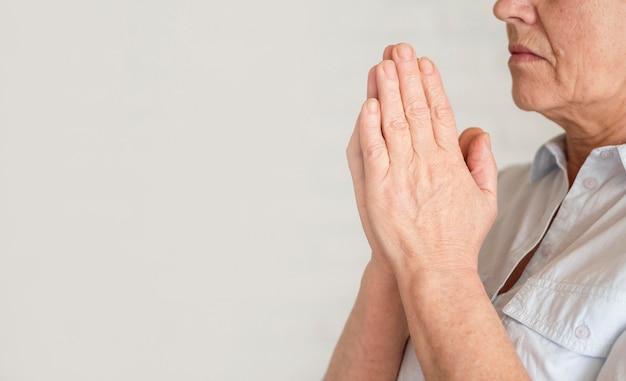 Vista lateral de la mujer rezando con espacio de copia