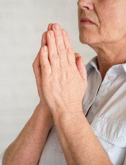 Vista lateral de la mujer rezando