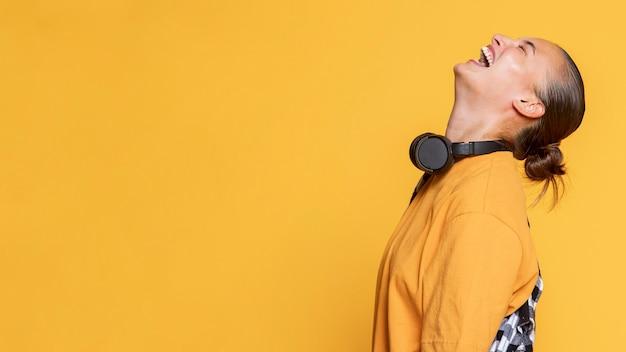 Vista lateral de la mujer riendo con auriculares