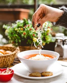 Vista lateral, una mujer rocía sopa de tomate, queso rallado y galletas