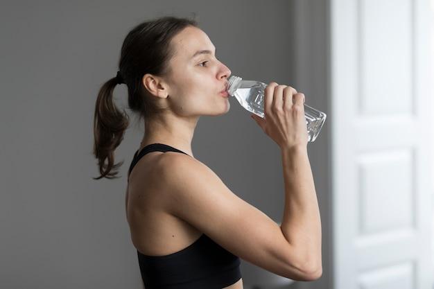 Vista lateral, de, mujer, en, ropa deportiva, agua potable