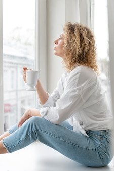 Vista lateral de la mujer rubia de pelo rizado relajándose en casa con una taza de café
