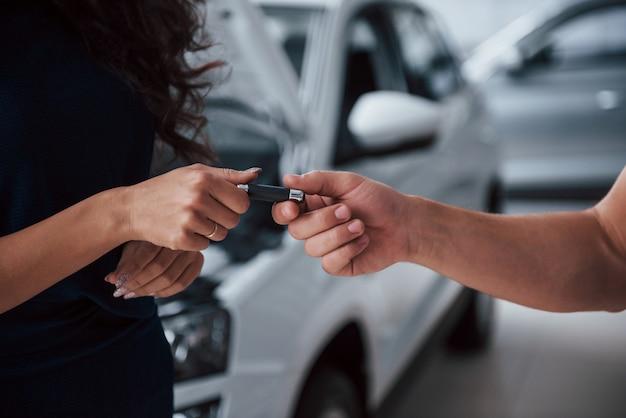Vista lateral. mujer en el salón del automóvil con el empleado tomando su coche reparado