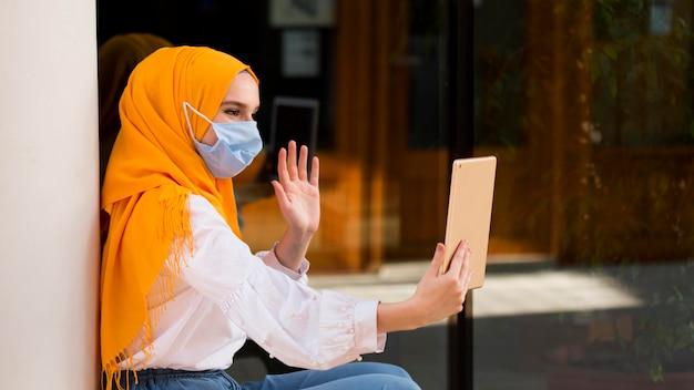 Vista lateral mujer saludando a tableta