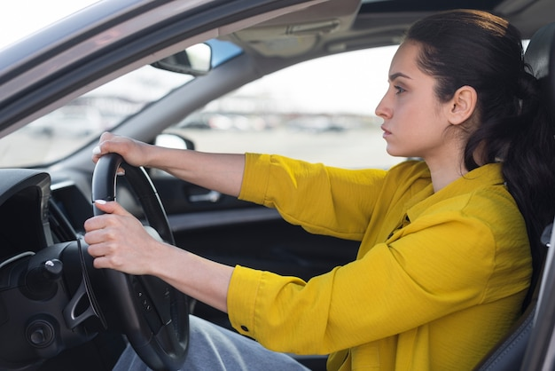 Vista lateral mujer segura conduciendo su coche