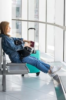 Vista lateral de la mujer sentada en el aeropuerto