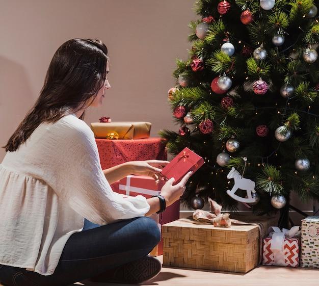 Vista lateral mujer sentada junto al árbol de navidad y regalos
