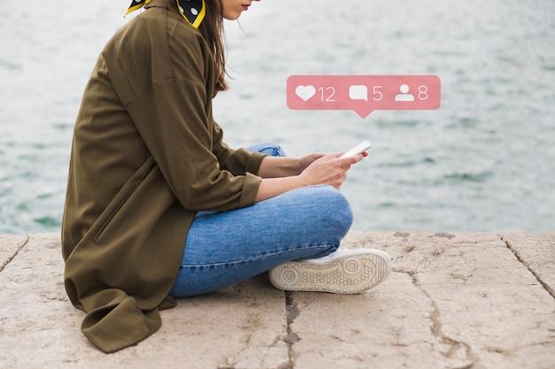 Vista lateral de la mujer sentada en el muelle con aplicación de redes sociales en el teléfono móvil