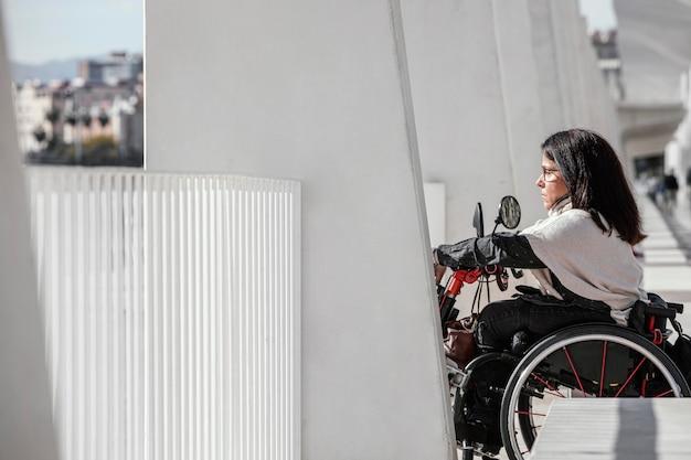 Vista lateral de la mujer en silla de ruedas en la ciudad