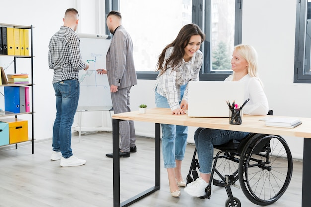 Vista lateral de la mujer en silla de ruedas conversando con una compañera de trabajo en la oficina