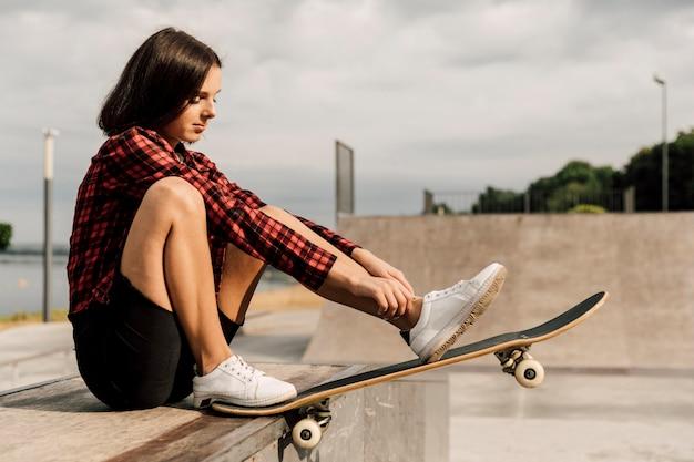 Vista lateral de la mujer en el skate park