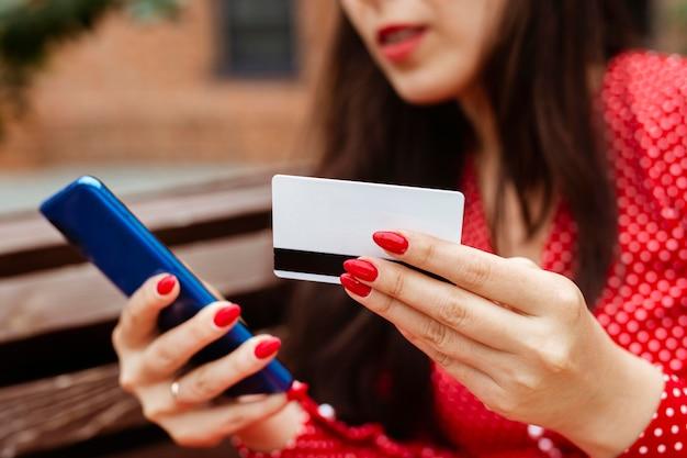Vista lateral de la mujer con smartphone y compra online con tarjeta de crédito