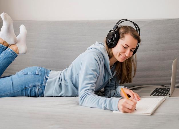 Vista lateral de la mujer en el sofá asistiendo a clase en línea
