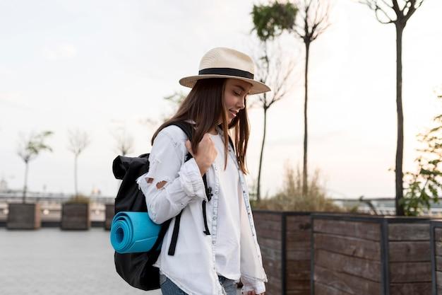 Vista lateral de la mujer con sombrero y mochila mientras viaja
