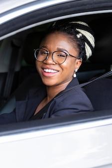 Vista lateral de la mujer sonriendo mientras conduce su coche