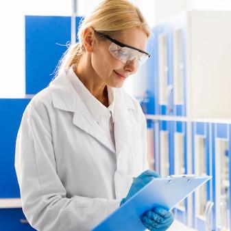 Vista lateral de la mujer sonriente científico con guantes quirúrgicos en el laboratorio