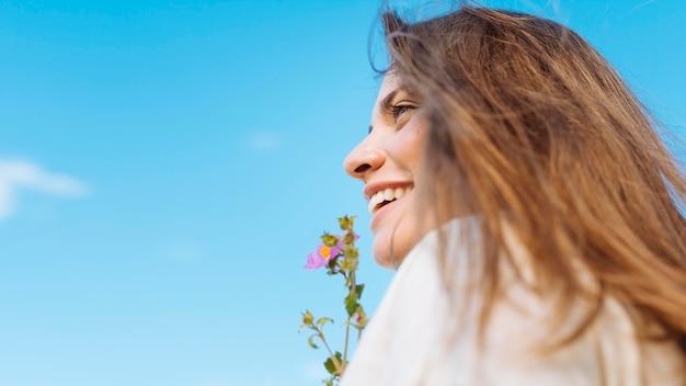 Vista lateral de la mujer sonriente con espacio de copia y flor