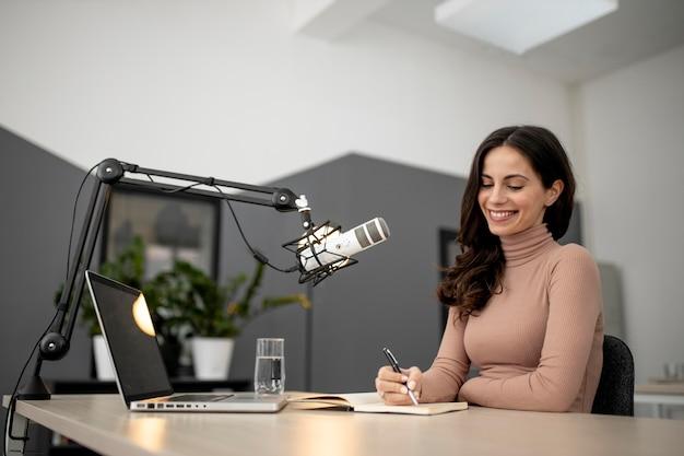 Vista lateral de la mujer sonriente en un estudio de radio con portátil y micrófono