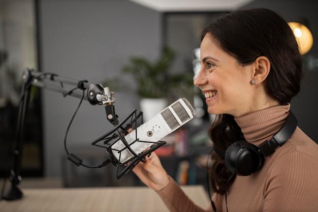 Vista lateral de la mujer sonriente haciendo radio