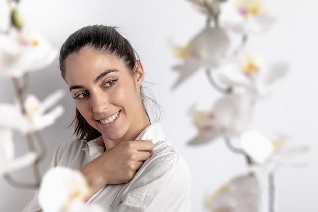 Vista lateral de la mujer sonriente con orquídeas desenfocadas