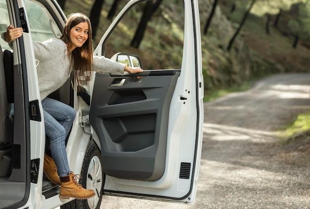 Vista lateral de la mujer sonriente saliendo del coche durante un viaje por carretera
