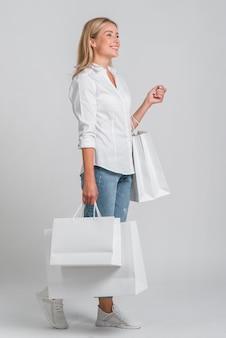 Vista lateral de la mujer sonriente sosteniendo un montón de bolsas de la compra.