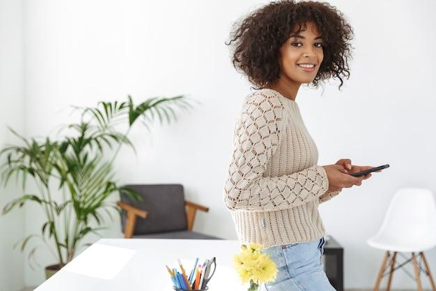 Vista lateral de una mujer sonriente vestida con ropa casual sosteniendo un teléfono inteligente y mirando a la cámara mientras está de pie cerca de la mesa en la oficina