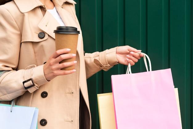 Vista lateral de la mujer sosteniendo café y bolsas de compras