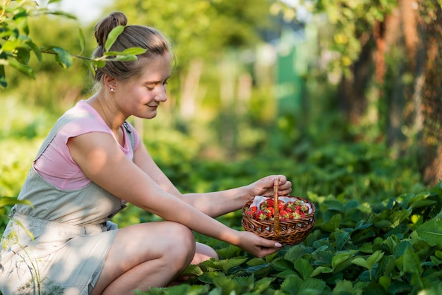 Vista lateral mujer sosteniendo cesta de frutas