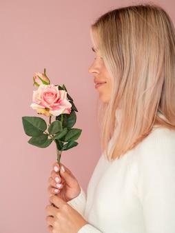 Vista lateral mujer sosteniendo hermosa rosa