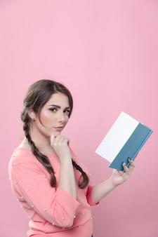 Vista lateral de la mujer sosteniendo un libro y actuando de manera inteligente