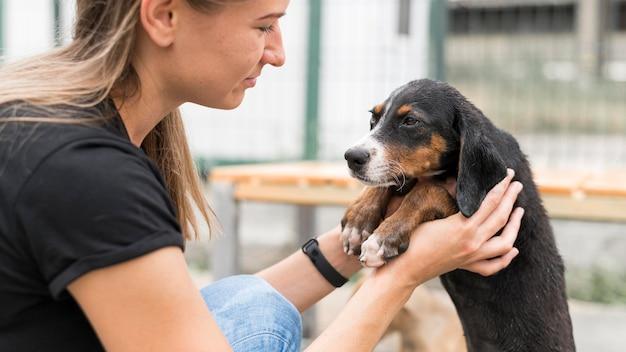 Vista lateral de la mujer sosteniendo lindo perro de rescate en el refugio