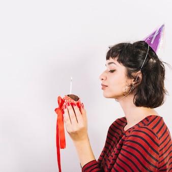 Vista lateral de una mujer sosteniendo un pastel con una cinta y una vela brillante cerca de su cara