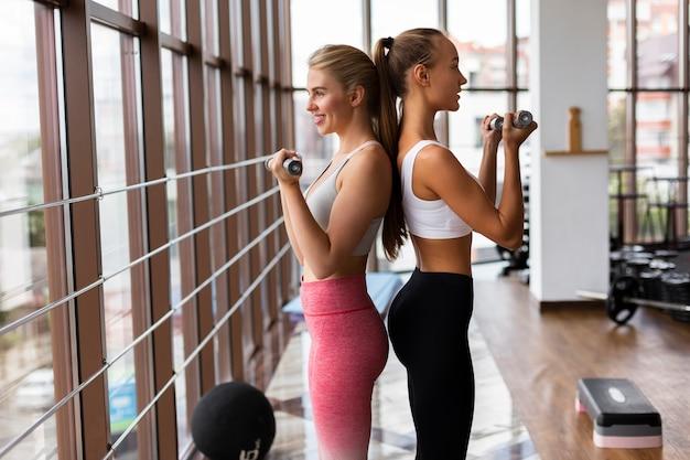 Vista lateral de la mujer sosteniendo pesas