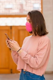 Vista lateral mujer sosteniendo smartphone