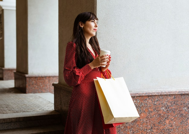 Vista lateral de la mujer sosteniendo una taza de café y bolsas de la compra.