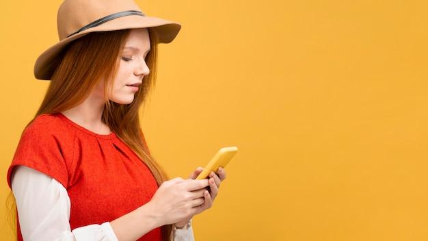 Vista lateral mujer sosteniendo teléfono