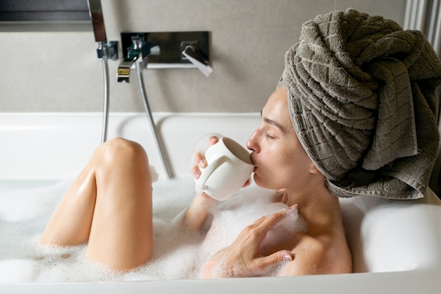 Vista lateral mujer con taza en bañera