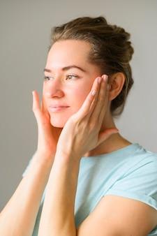 Vista lateral de la mujer tocando su rostro después de aplicar la crema