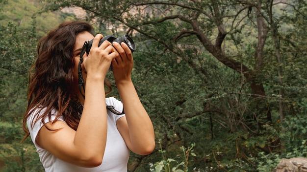 Vista lateral mujer tomando fotos de la naturaleza