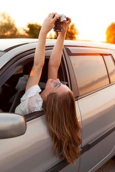 Vista lateral de la mujer tomando un selfie con cámara mientras está en el coche