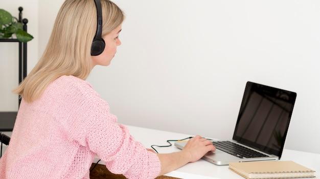 Vista lateral mujer trabajando con auriculares en