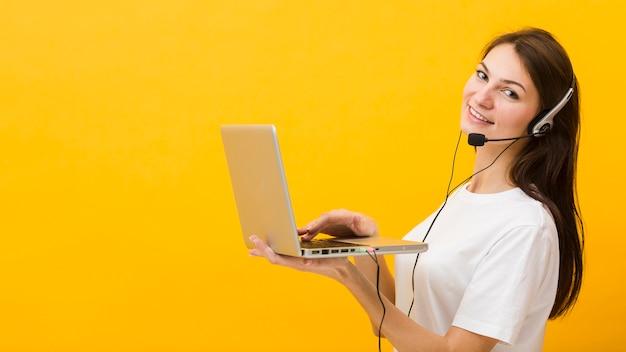 Vista lateral de la mujer usando auriculares sonriendo y sosteniendo portátil
