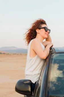 Vista lateral mujer en la ventanilla del coche