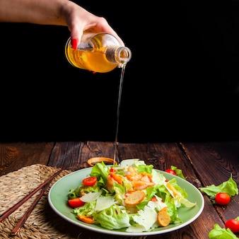 Vista lateral mujer vertiendo aceite en ensalada deliciosa en placa sobre fondo de madera y negro.
